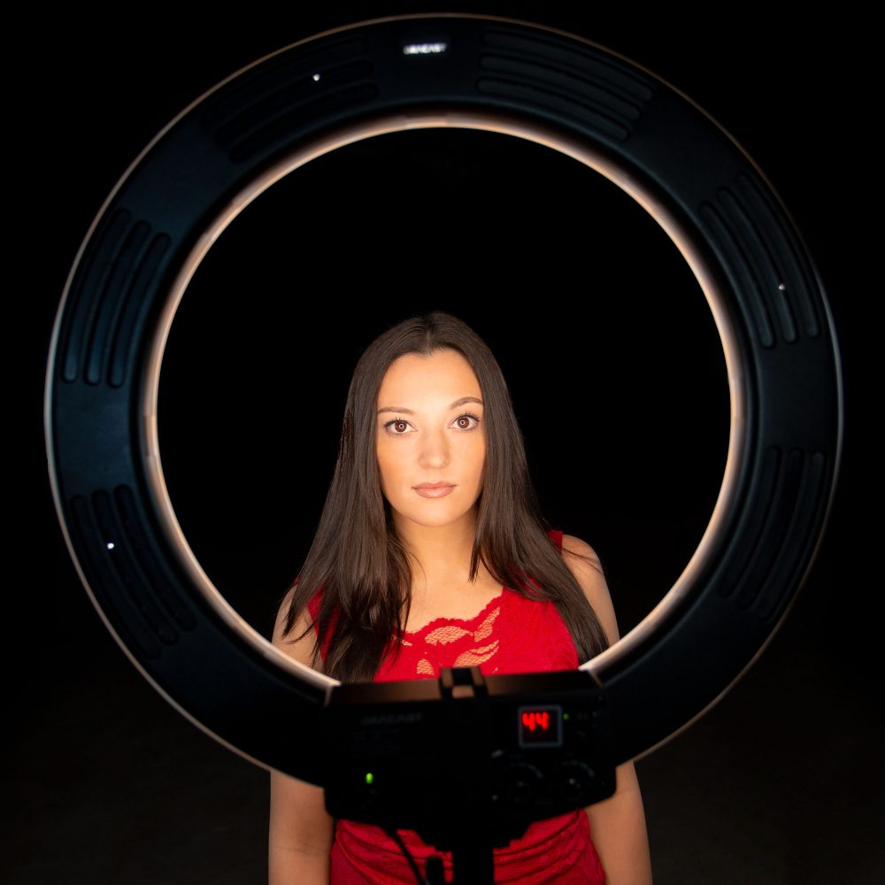 Front view of a model posing with a Dracast LED video ring light