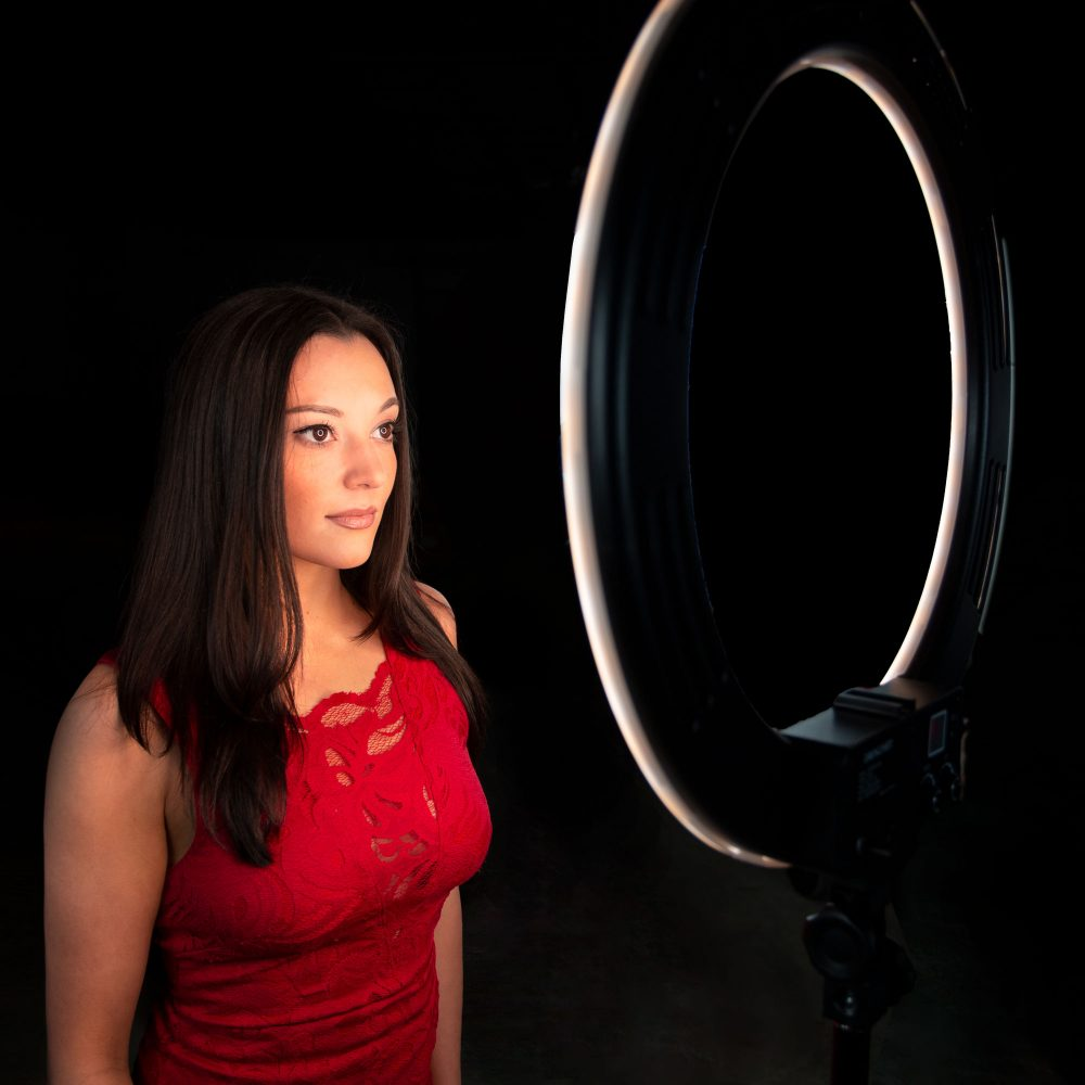 Model posing in front of a Dracast LED video ring light