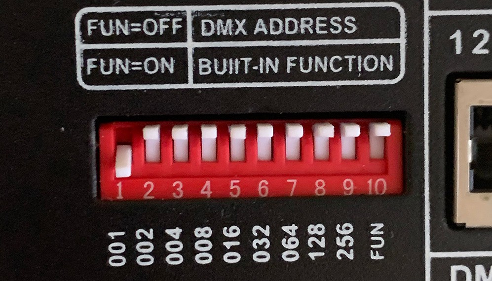 A DMX dip switch set on the back of a DMX control board